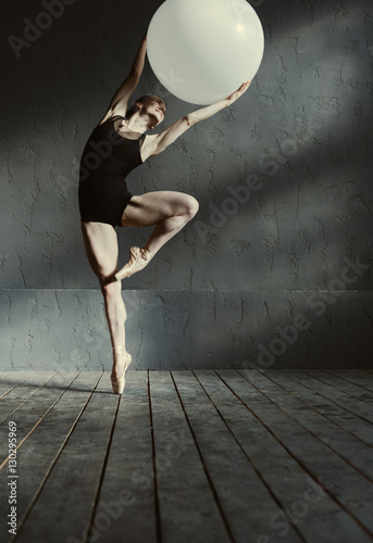 Fototapeta  Inspired young gymnast stretching using the white ball