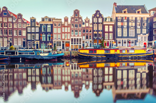 Foto auf Acrylglas Amsterdam Amsterdam canal Singel with typical dutch houses and houseboats during morning blue hour, Holland, Netherlands. Used toning