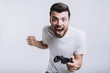 canvas print picture - Young guy with beard holding joystick pretending he is playing games