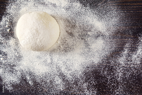 Fotografie, Obraz  Ball of pizza dough on a rustic wooden background