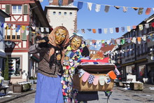 Couple In Traditional Costumes Of Witch And Spattleshansel With A Buggy, Swabian Alemannic Carnival, Gengenbach, Black Forest, Baden Wurttemberg, Germany