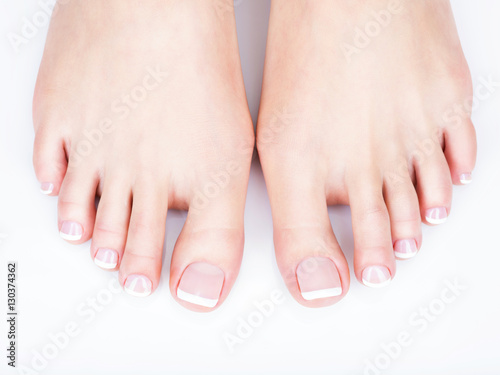 Poster Pedicure female feet with white french pedicure on nails. at spa salon