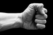 Сlenched fist on a black background. Man's hand