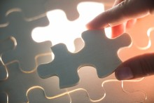 Woman Placing Missing Piece In Jigsaw Puzzle