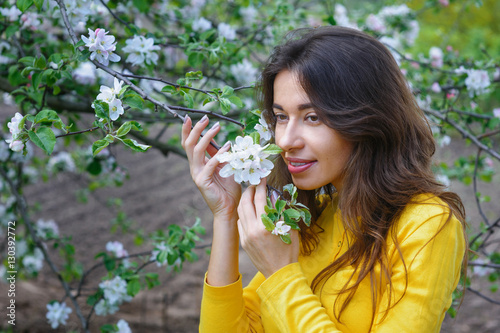 Foto op Aluminium Kasteel young beautiful woman near the blossoming Spring Garden tree