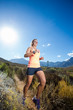Wide angle view of a fit trail running female athlete running on a trail in the hills with dry shrubs on a bright sunny day