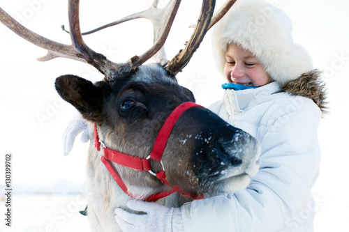 obraz PCV Happy little girl hugging her reindeer. Winter playtime.