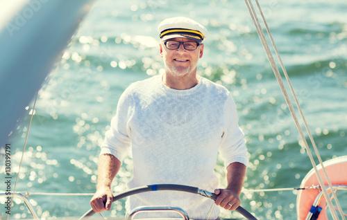 Fényképezés  senior man at helm on boat or yacht sailing in sea
