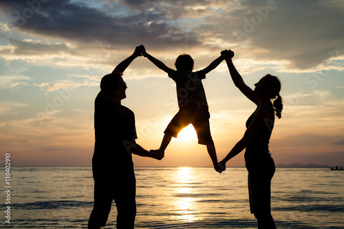 Papiers peints Corail Silhouette of happy family who playing on the beach at the sunse