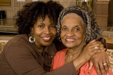 Portrait Of A Senior Woman Hugging Her Daughter.
