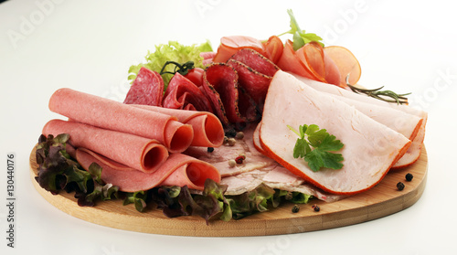 Staande foto Vlees Food tray with delicious salami, pieces of sliced ham, sausage, tomatoes, salad and vegetable - Meat platter with selection