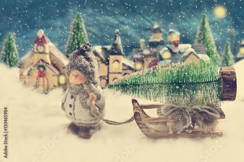 Fotografie, Obraz  winter night scene with a boy pulling a slad with christmas tree