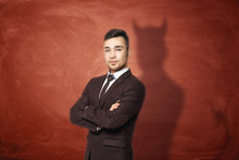 Businessman In Suit Standing With His Arms Folded, He Is Casting Shadow Of The Devil On The Rusty Orange Wall Behind Him.