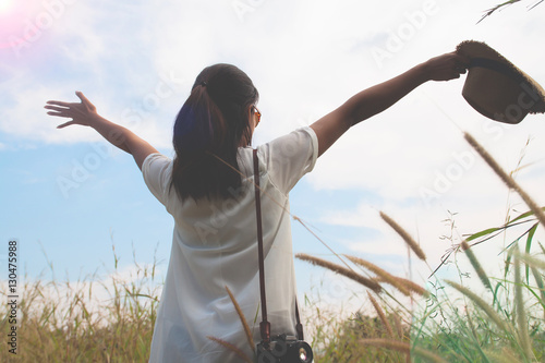woman traveler with camera holding hat and breathing at field of yard and forest Wallpaper Mural