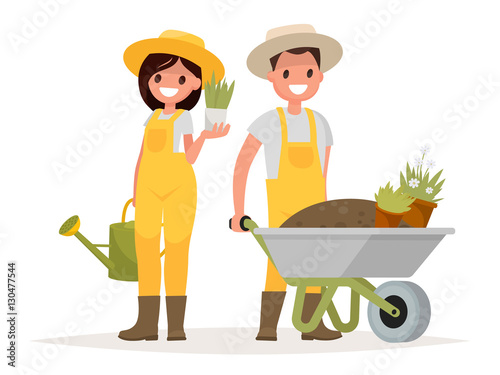 Photographie A couple of gardeners. Man with wheelbarrow of earth, a woman ho