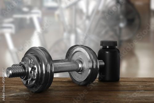 Foto op Plexiglas Fitness Dumbbells on table against blurred gym interior background