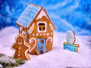 Christmas cookie house with blue roof in snow on winter background. Gingerbread man and gingerbread cookie snowman next to gingerbread house.