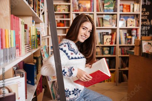 Keuken foto achterwand Berlijn Smiling student reading a book at bookshelf in the library
