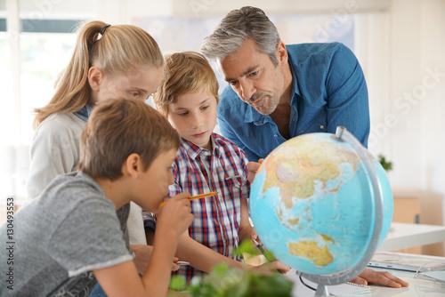 Obraz na płótnie Teacher with kids in geography class looking at globe
