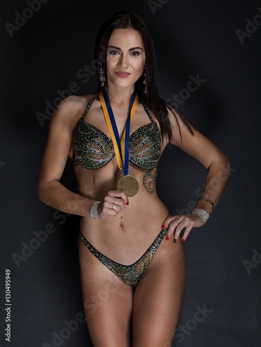 Valokuva  beautiful woman bodybuilder with medals on a black background