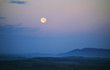 Leinwanddruck Bild - Twilight scenery. Moon rising over hills through the clouds on evening sky, minimal landscape