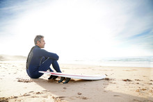 Surfer Sitting On Sandy Beach Looking At The Ocean