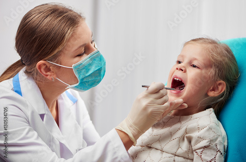 woman-dentist-in-mask-doing-teeth-checkup-of-little-girl-in-dental-room-health-care-and-medicine-concept