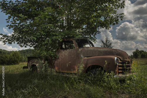 Abandoned car on grassy field by tree at dusk