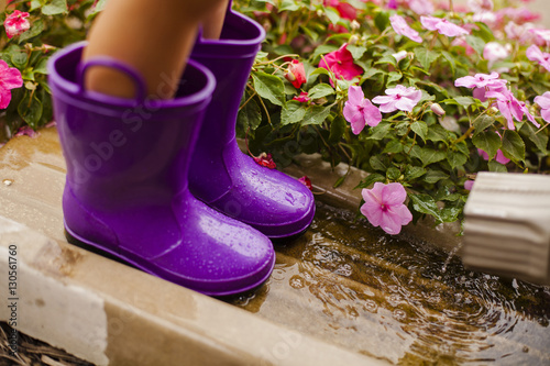 Low section of girl wearing purple rubber boots while standing in yard