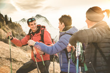 Friends Group Trekking On French Alps At Sunset - Hikers With Backpacks And Sticks Walking On Mountain - Wanderlust Travel Concept With Young People At Excursion In Wild Nature - Focus On Left Guy