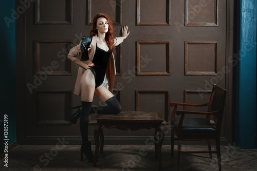 Fotografia, Obraz  Red-haired woman with a beautiful figure standing in the room.