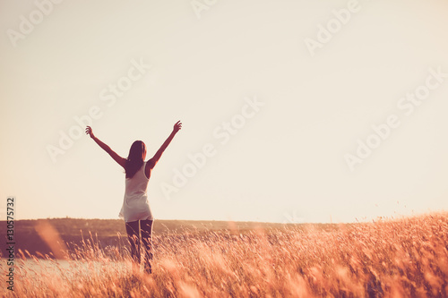 Fotografie, Obraz  Free woman raising arms to golden sunset