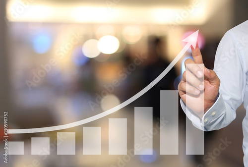 Pinturas sobre lienzo  Businessman to touch in peak of Business graph on abstract blur