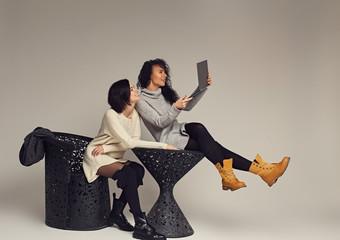 Two brunette women using la...