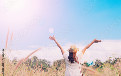 woman traveler with camera holding hat and breathing at field of grasses and for Canvas Print