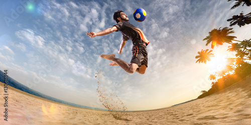 Beach soccer player in action. Sunny beach wide angle and sea