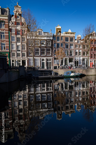 Photo Amsterdam's converted warehouses reflect in one of its canals