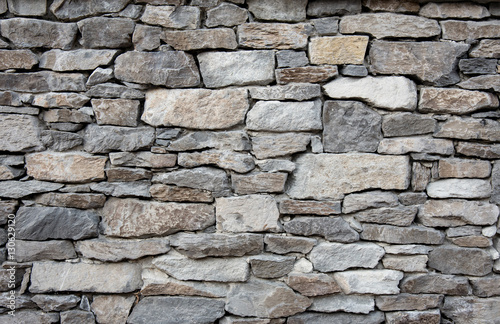 Grey stone wall with different sized stones, modern siding Fototapet