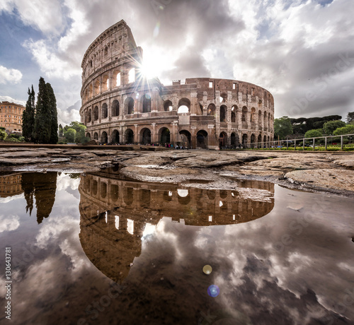 Cuadros en Lienzo Roman Colosseum at sunrise with full reflection and beautiful sky