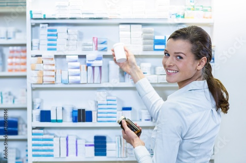 Pharmacist checking medicine in shelf at pharmacy