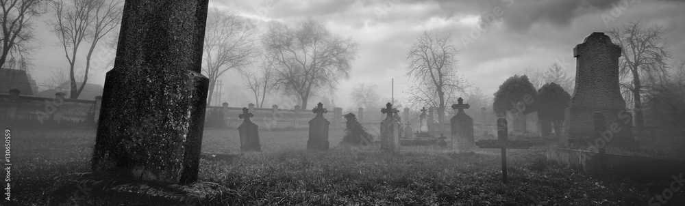Fototapeta Old creepy graveyard on stormy winter day in black and white