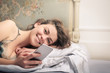 Happy woman using her phone in bed