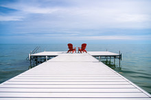 Red Adirondack Or Muskoka Chairs On The Dock Overlooking The Water At The Cottage