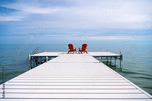 Red Adirondack or Muskoka Chairs on the dock overlooking the water at the cottag Fototapeta