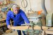 mature carpenter working at a workshop