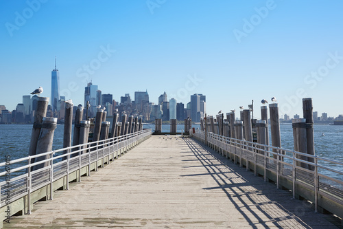 New York city skyline view and empty pier with seagulls in a sunlight Plakat