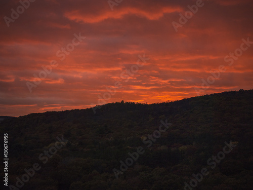 Hill silhouetted against orange sky at sunset