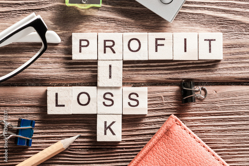 Fotografía  Profit loss and risk words on workplace collected of wooden cubes