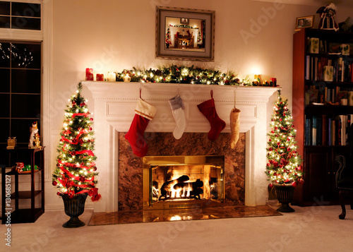 Living room decked out for the Christmas holidays with trees, stockings and a wa Canvas Print