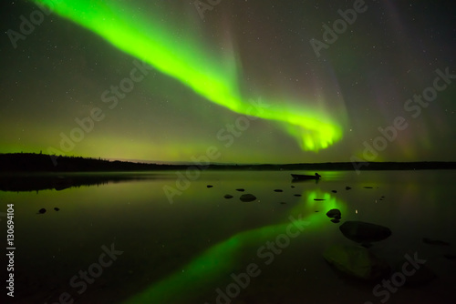Photo  Aurora Borealis and Starry Sky - Multi-colored aurora borealis bright up the starry night sky above a quiet lake